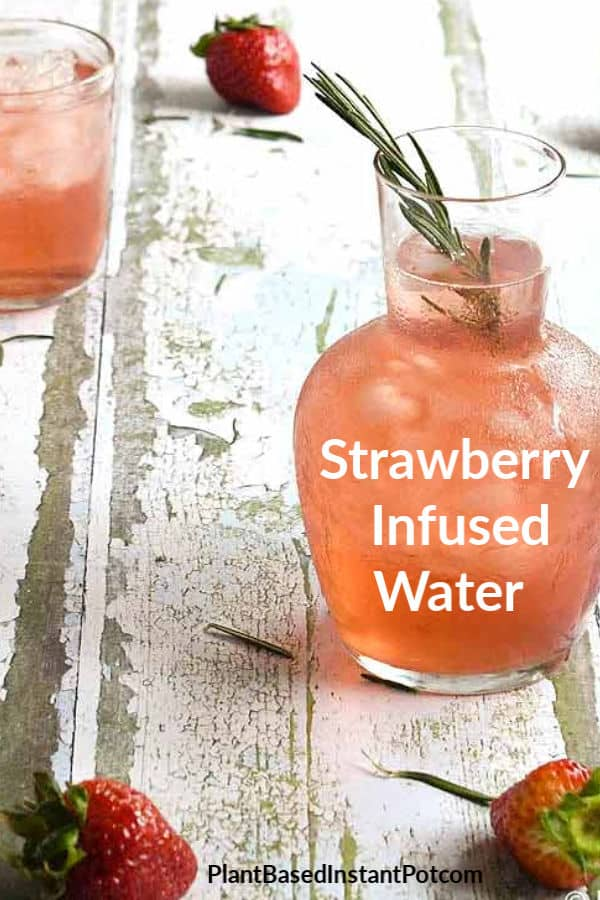Strawberry Infused water with rosemary in a glass carafe and glass.