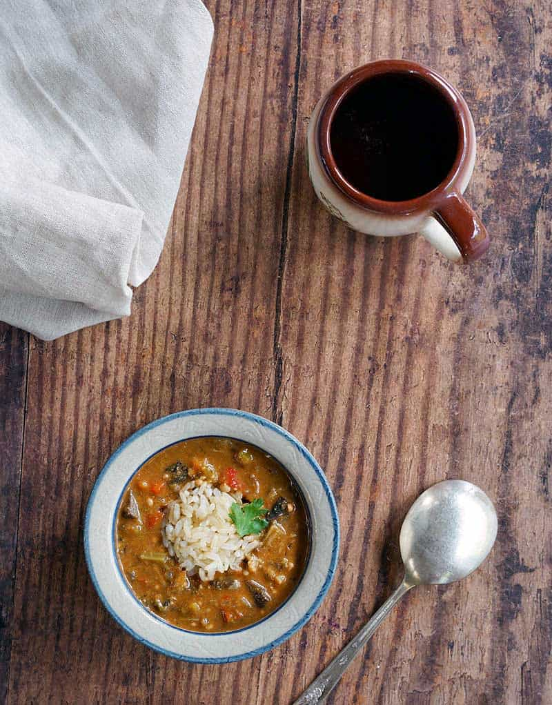 Instant Pot Oil-Free Mushroom Gumbo in a red wing pottery bowl topped with brown rice