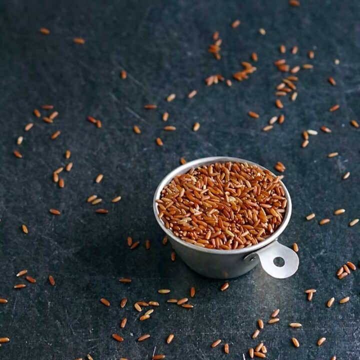 Uncooked whole grain red rice in a tin measuring cup with grains scattered on a table.