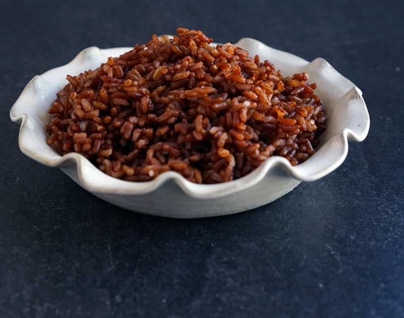Cooked red rice in white ceramic pie plate