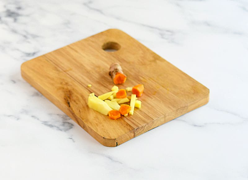 Fresh turmeric and fresh ginger on a wooden cutting board