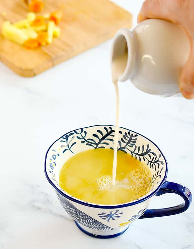 Vegan Nondairy creamer being poured into a cup with Turmeric Ginger Tea Concentrate