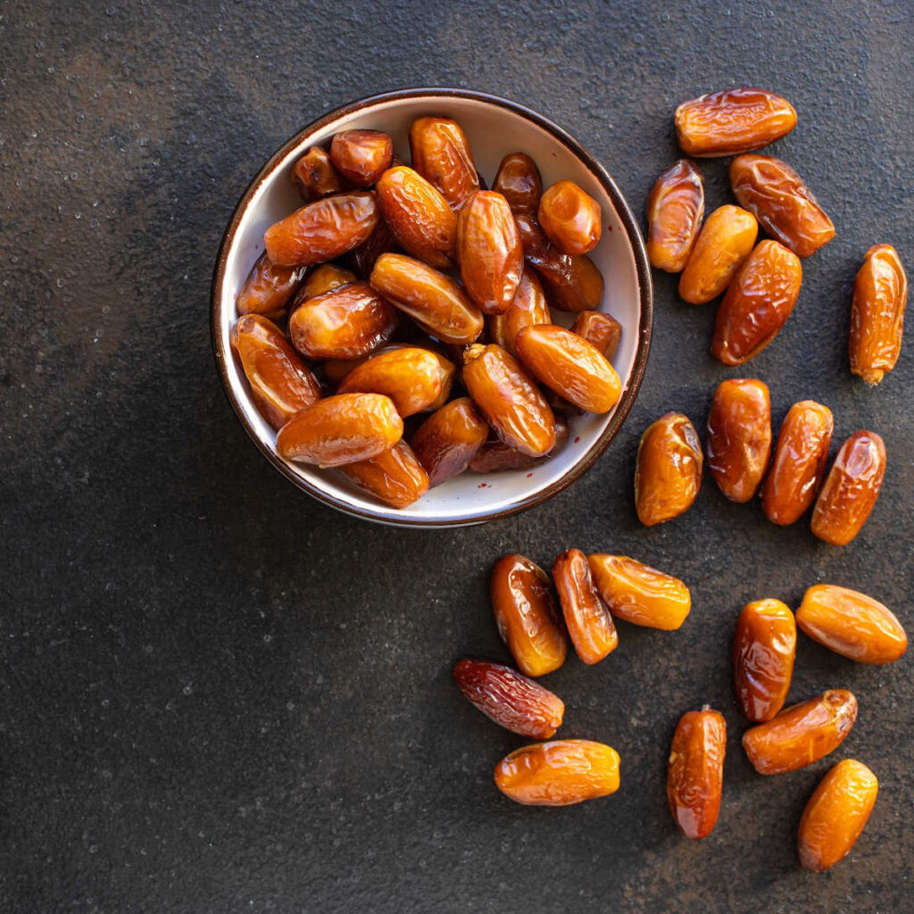 Dates in a metal bowl on a dark cement table.